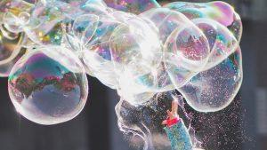 Kind lässt Seifenblasen platzen